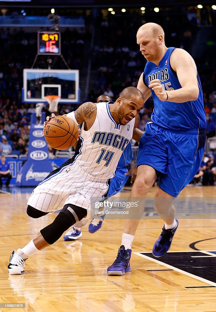 Jameer Nelson #14 of the Orlando Magic drives against Chris Kaman #35 of the Dallas Mavericks during the game at Amway Center on January 20, 2013 in Orlando, Florida.