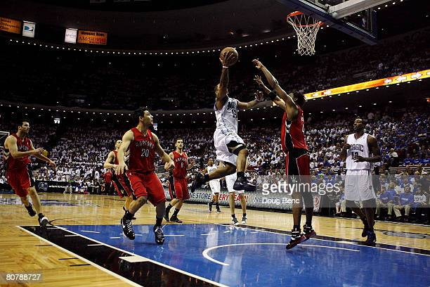 Jameer Nelson of the Orlando Magic scores over Chris Bosh and Jason Kapono of the Toronto Raptors in Game One of the Eastern Conference Quarterfinals...