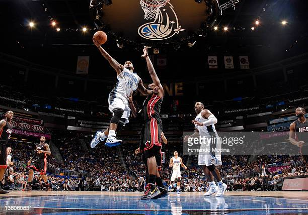 Jameer Nelson of the Orlando Magic shoots the basketball against Chris Bosh of the Miami Heat during the preseason game on December 21 2011 at Amway...