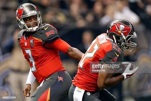 Jameis Winston hands the ball to Doug Martin of the Tampa Bay Buccaneers during the first quarter of a game against the New Orleans Saints at the...