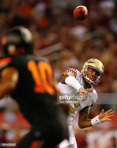 Jameis Winston of the Florida State Seminoles passes against the Oklahoma State Cowboys in the first half of the Advocare Cowboys Classic at ATT...