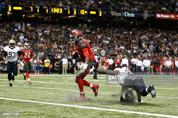 Jameis Winston of the Tampa Bay Buccaneers avoids a tackle by Bobby Richardson of the New Orleans Saints as he rushes for a touchdown during the...