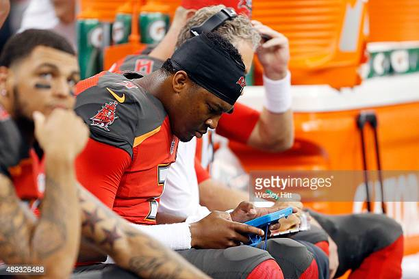 Jameis Winston of the Tampa Bay Buccaneers reviews plays on the sideline during the first quarter of a game against the New Orleans Saints at the...