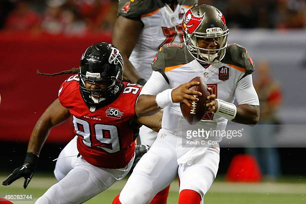 Jameis Winston of the Tampa Bay Buccaneers scrambles away from Adrian Clayborn of the Atlanta Falcons during the first half at the Georgia Dome on...