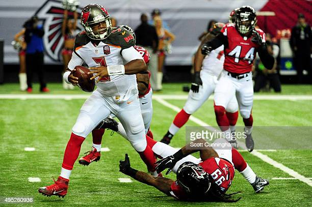 Jameis Winston of the Tampa Bay Buccaneers slips a tackle by Adrian Clayborn of the Atlanta Falcons during the first half at the Georgia Dome on...