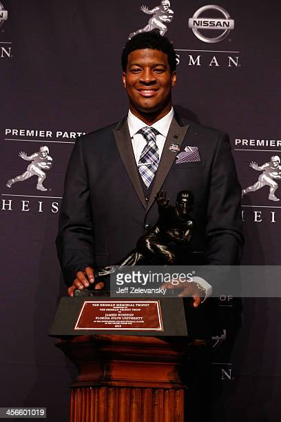 Jameis Winston quarterback of the Florida State Seminoles poses with the trophy during a press conference after the 2013 Heisman Trophy Presentation...