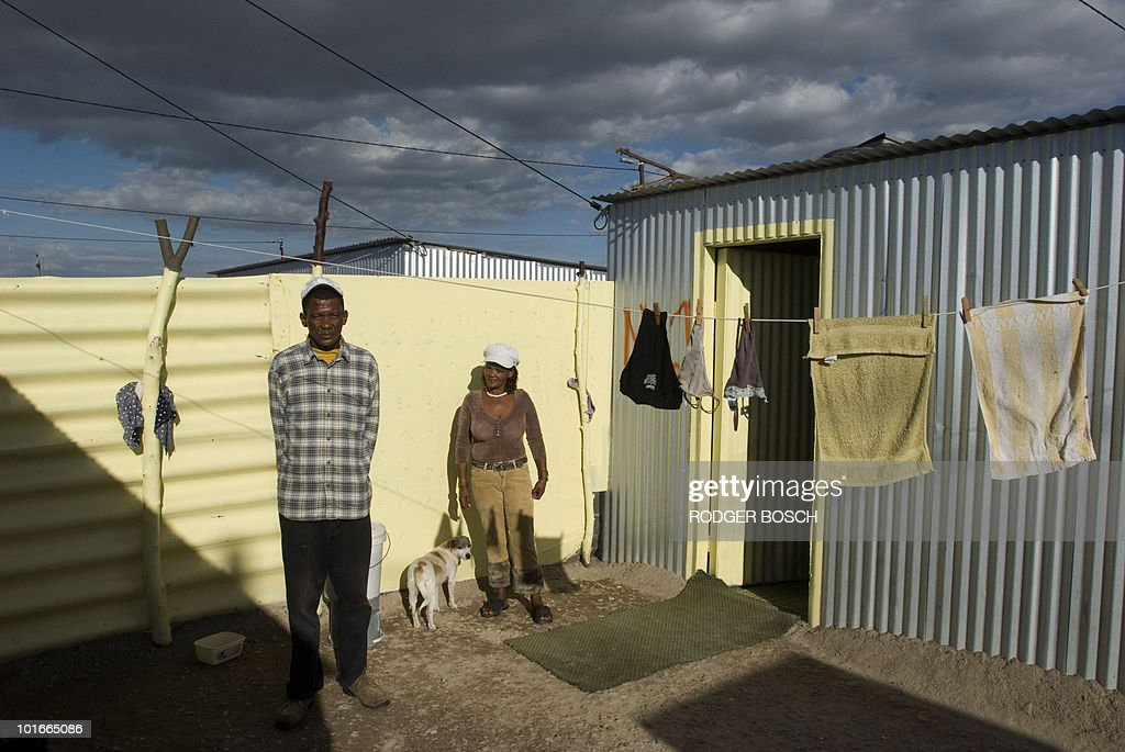 James Adams (L) and Rina Mina Kiwido, stand outside their home in Blikkiesdorp ('Tin Can Town' in Afrikaans), a settlement of corrugated iron houses, on April 20, 2010 about 25Km East of Cape Town, South Africa. South Africa has poured billions into hosting Africa's first football World Cup with new stadiums, transport systems and a beefed up police force. But while children gleefully undergo football training on a sandy patch near a busy road, there is little sign in Blikkiesdorp of the World Cup kick-off on June 11.