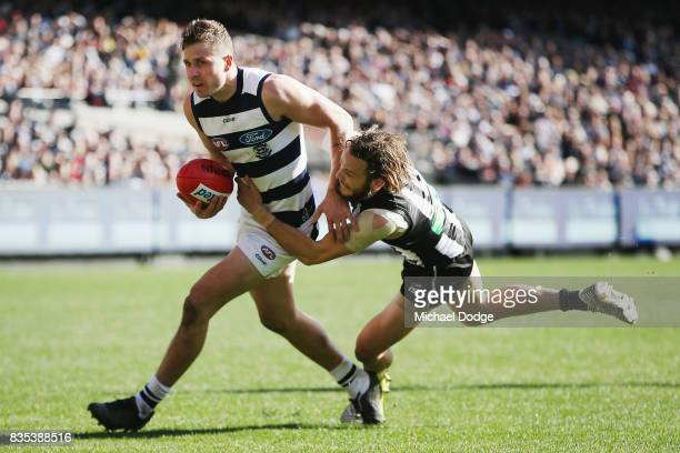 James Aish of the Magpies tackles Mitch Duncan of the Cats during the round 22 AFL match between the Collingwood Magpies and the Geelong Cats at...