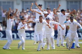 James Anderson of England celebrates the final wicket of Brad Haddin of Australia and victory with team mates during day five of the 1st Investec...