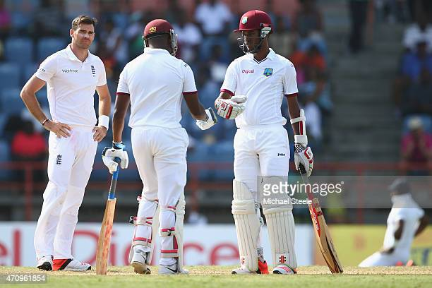 James Anderson of England looks towards Darren Bravo and Kraigg Brathwaite of West Indies as they build a high scoring second wicket partnership...