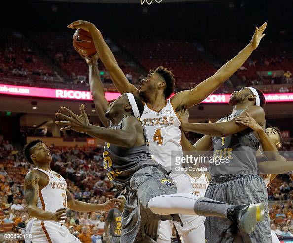 James Banks of the Texas Longhorns blocks a shot by Jimmy Hall of the Kent State Golden Flashes as Adonis De La Rosa of the Kent State Golden looks...