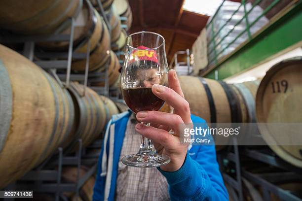 James Bardgett checks the quality of beer which is stored in barrels at the Wild Beer Co brewery at Lower Westcombe Farm on February 11 2016 near...