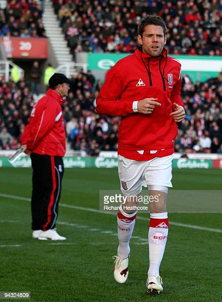 James Beattie of Stoke warms up as manager Tony Pulis watches the game during the Barclays Premier League match between Stoke City and Wigan Athletic...