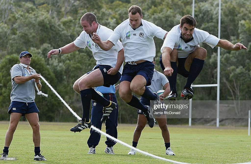 James Beattie Stuart Grimes and Jason White of Scotland skip over a rope during Scotland training at Lighthouse Park on October 14 2003 in Caloundra...