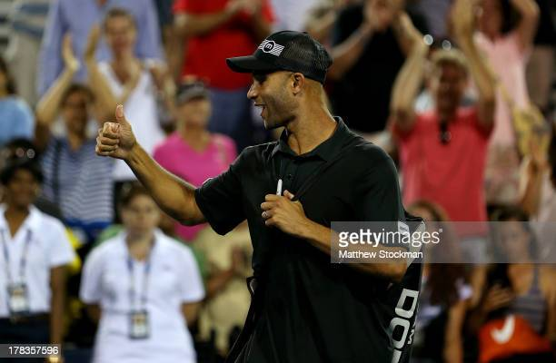 James Blake of the United States of America salutes the crowd as he walks off court with partner Jack Sock of the United States of America following...
