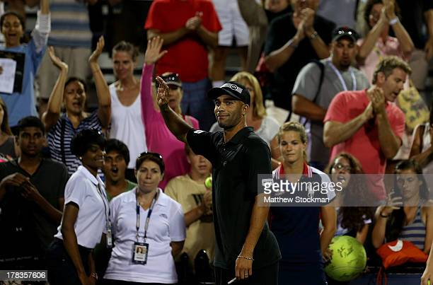 James Blake of the United States of America waves to the crowd as he walks off court with partner Jack Sock of the United States of America following...