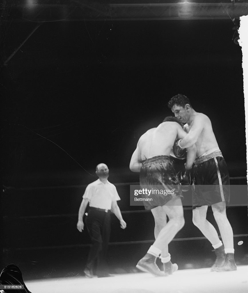 James Braddock (right), his face bruised and swollen, hangs onto Joe Louis in a clinch in the seventh round of their title bout in Chicago.