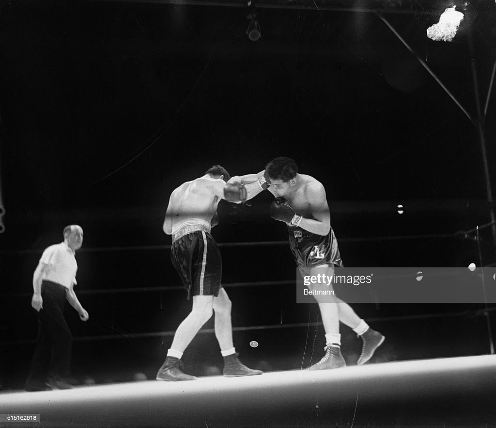James Braddock (left) lands a right to the head, while Joe Louis misses with a right in the second round of their title fight in Chicago. Braddock was going strong at this stage of the battle but was kayoed in 1:10 of the eighth round by Louis.