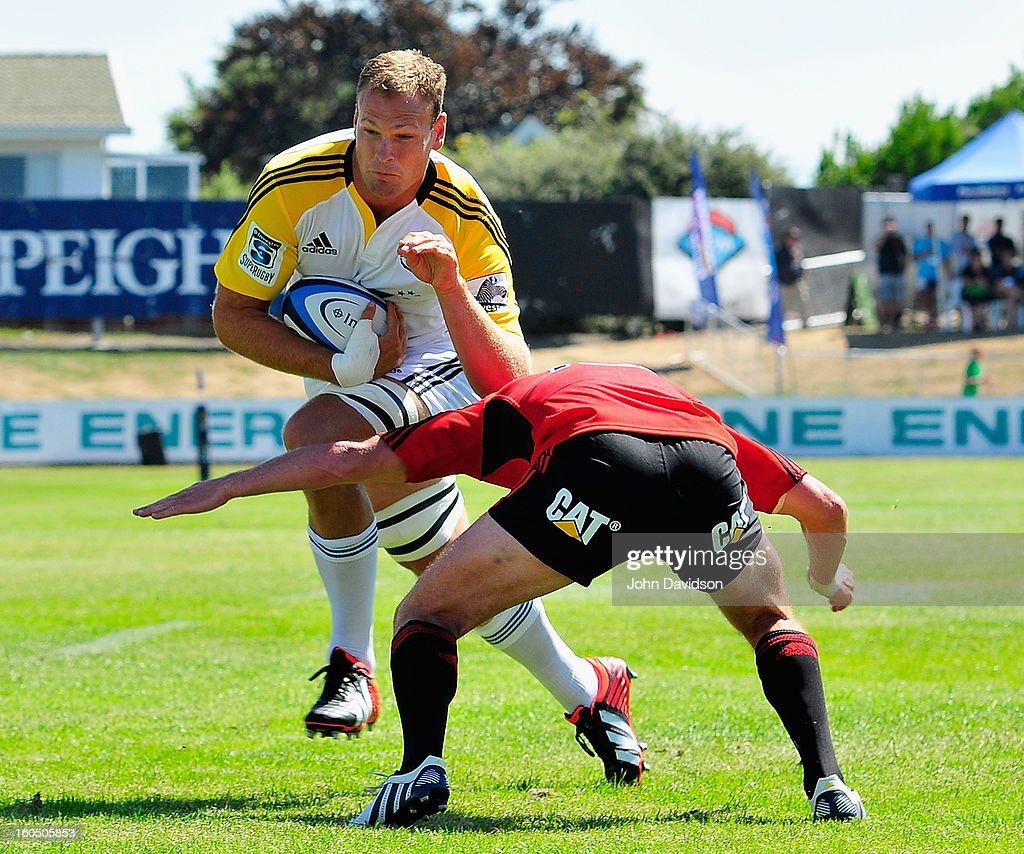 James Broadhurst of the Hurricanes breaks the tackle by Tom Marshall of the Crusaders during the 2013 Super Rugby pre-season friendly match between the Crusaders and the Hurricanes at Alpine Stadium on February 2, 2013 in Timaru, New Zealand.