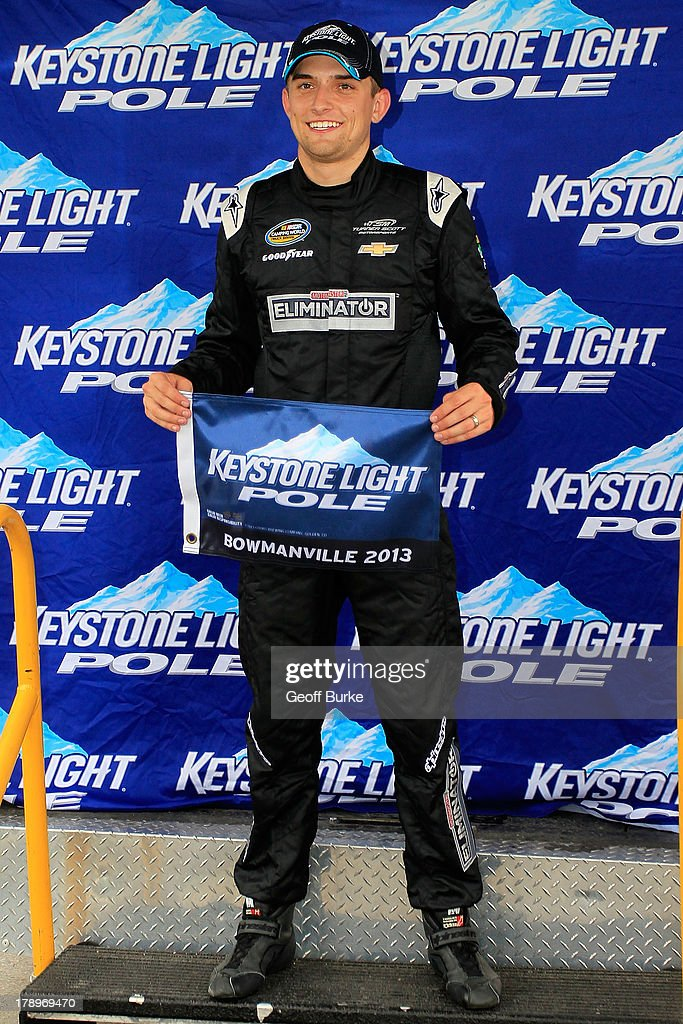 <a gi-track='captionPersonalityLinkClicked' href=/galleries/search?phrase=James+Buescher&family=editorial&specificpeople=5409134 ng-click='$event.stopPropagation()'>James Buescher</a>, driver of the #31 Motomaster Eliminator Chevrolet, holds the pole award flag after capturing the pole position for the NASCAR Camping World Truck Series Chevrolet Silverado 250 at Canadian Tire Motorsport Park on August 31, 2013 in Bowmanville, Canada.