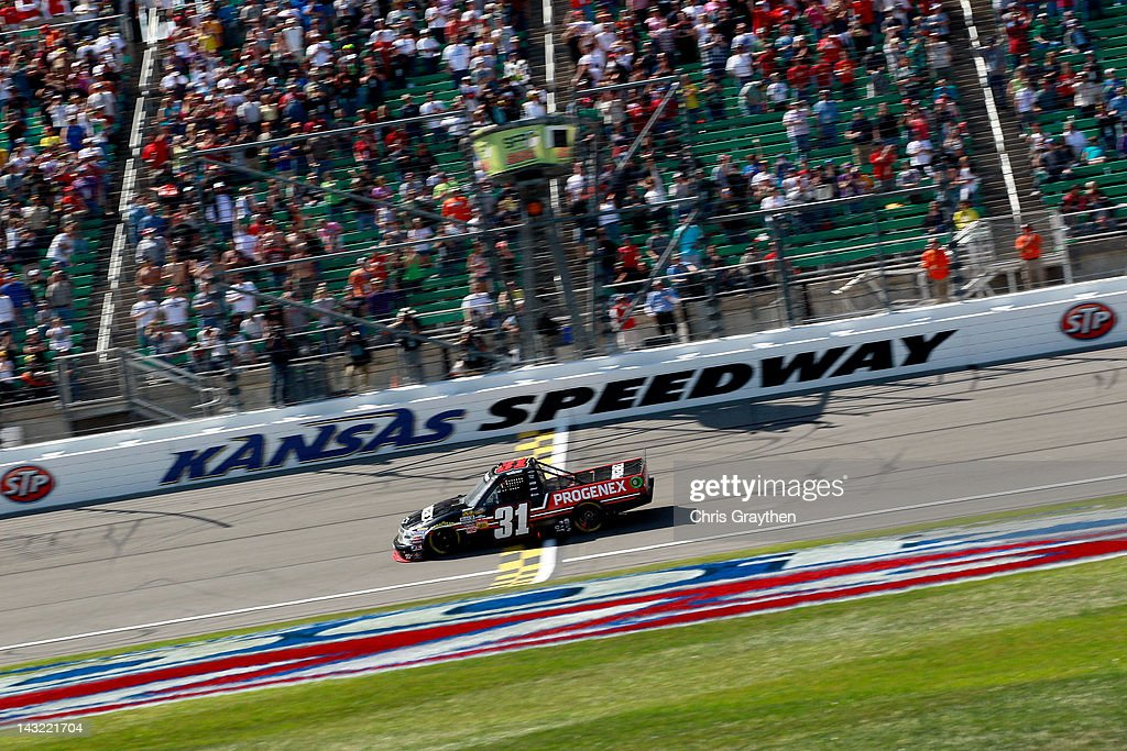 James Buescher, driver of the #31 Progenex Chevrolet, heads across the start/finish line to take the checkered flag and win the NASCAR Camping World Series SFP 250 at Kansas Speedway on April 21, 2012 in Kansas City, Kansas.