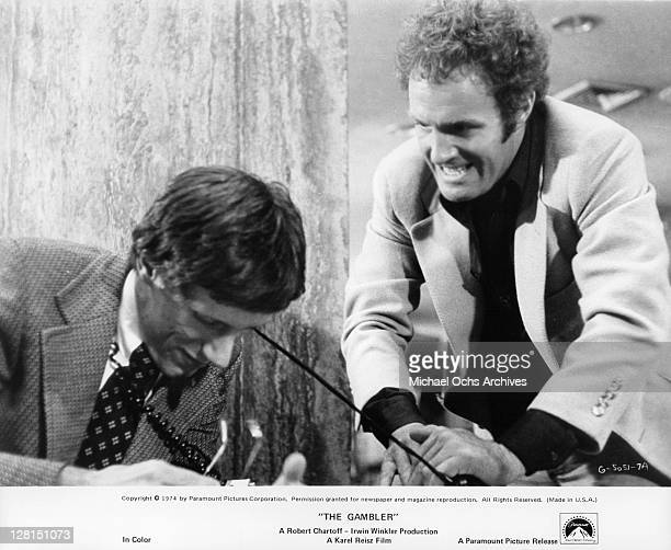 James Caan angrily pulls the telephone wire around James Woods in a scene from the film 'The Gambler' 1974
