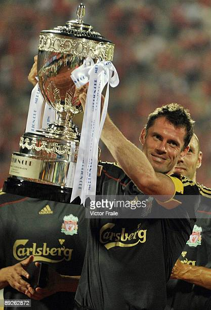 SINGAPORE JULY 26 James Carrager of Liverpool holds the trophy after winning their preseason friendly soccer match between Singapore and Liverpool at...