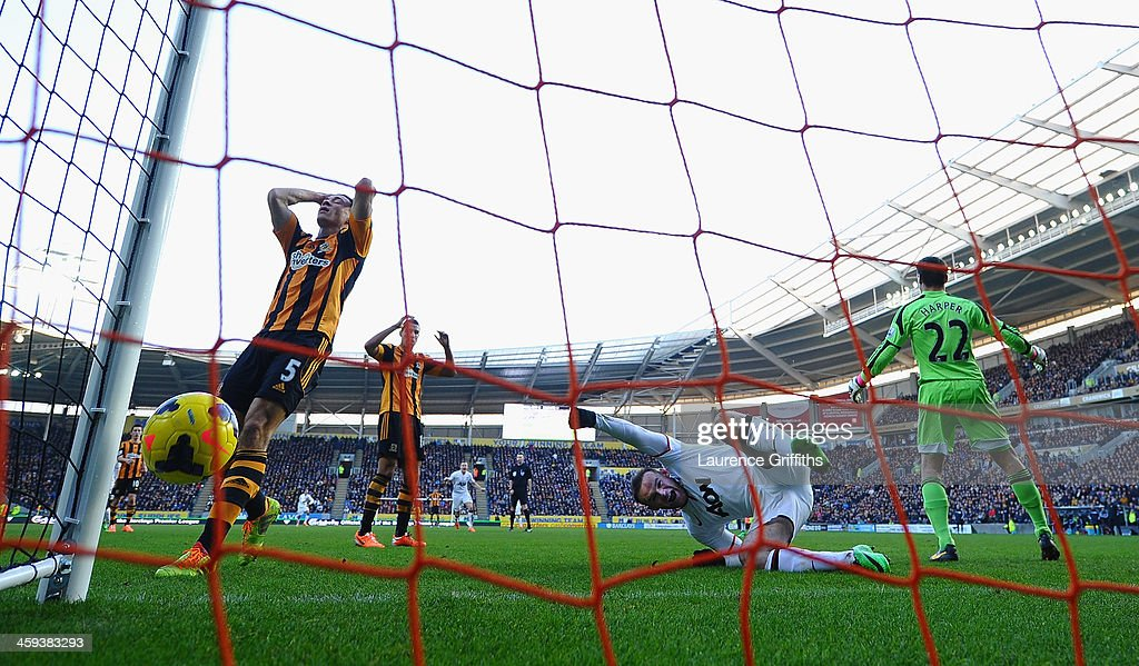 James Chester of Hull scores an own goal as <a gi-track='captionPersonalityLinkClicked' href=/galleries/search?phrase=Wayne+Rooney&family=editorial&specificpeople=157598 ng-click='$event.stopPropagation()'>Wayne Rooney</a> of Manchester United celebrates during the Barclays Premier League match between Hull City and Manchester United at KC Stadium on December 26, 2013 in Hull, England.