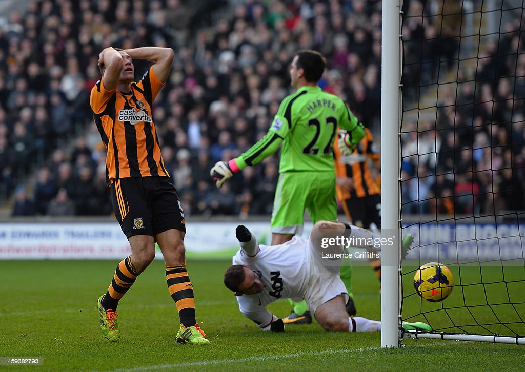 James Chester of Hull scores an own goal in front of Wayne Rooney of Manchester United during the Barclays Premier League match between Hull City and Manchester United at KC Stadium on December 26, 2013 in Hull, England.