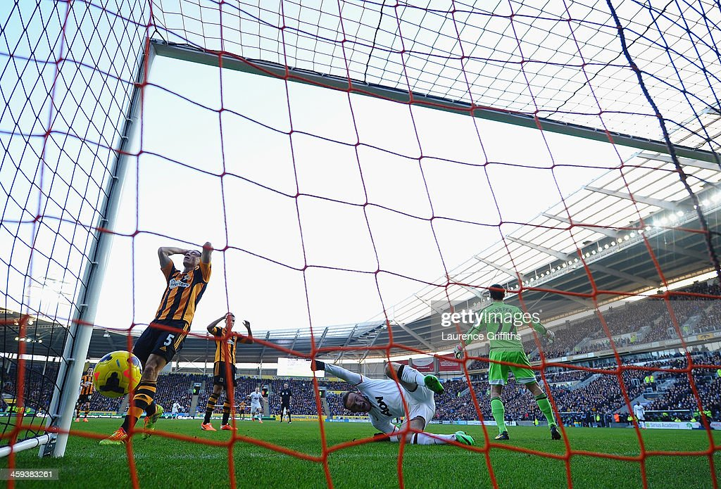James Chester of Hull scores an own goal in front of <a gi-track='captionPersonalityLinkClicked' href=/galleries/search?phrase=Wayne+Rooney&family=editorial&specificpeople=157598 ng-click='$event.stopPropagation()'>Wayne Rooney</a> of Manchester United during the Barclays Premier League match between Hull City and Manchester United at KC Stadium on December 26, 2013 in Hull, England.
