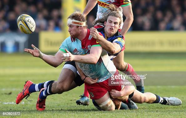 James Chisholm of Harlequins off loads the ball as Max Clark tackles during the Aviva Premiership match between Bath Rugby and Harlequins at the...