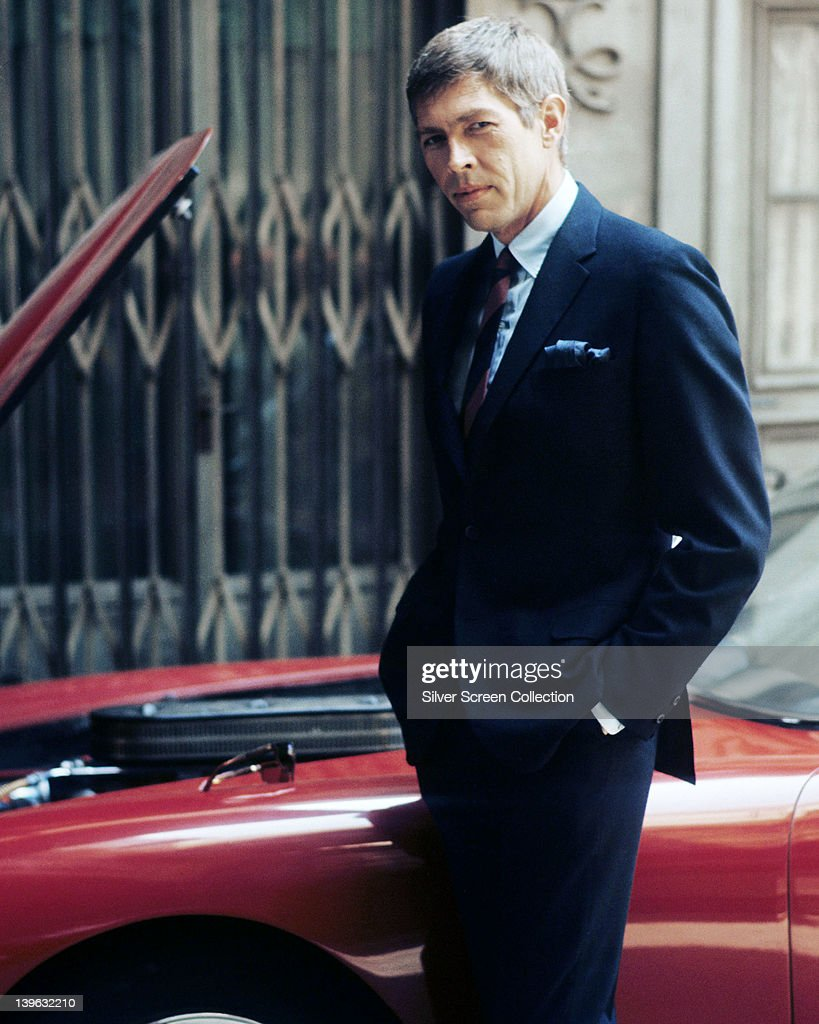 <a gi-track='captionPersonalityLinkClicked' href=/galleries/search?phrase=James+Coburn&family=editorial&specificpeople=221456 ng-click='$event.stopPropagation()'>James Coburn</a> (1928-2002), US actor, wearing a dark blue suit with his hands in the pockets of his trousers, posing beside a red sports car, circa 1970.