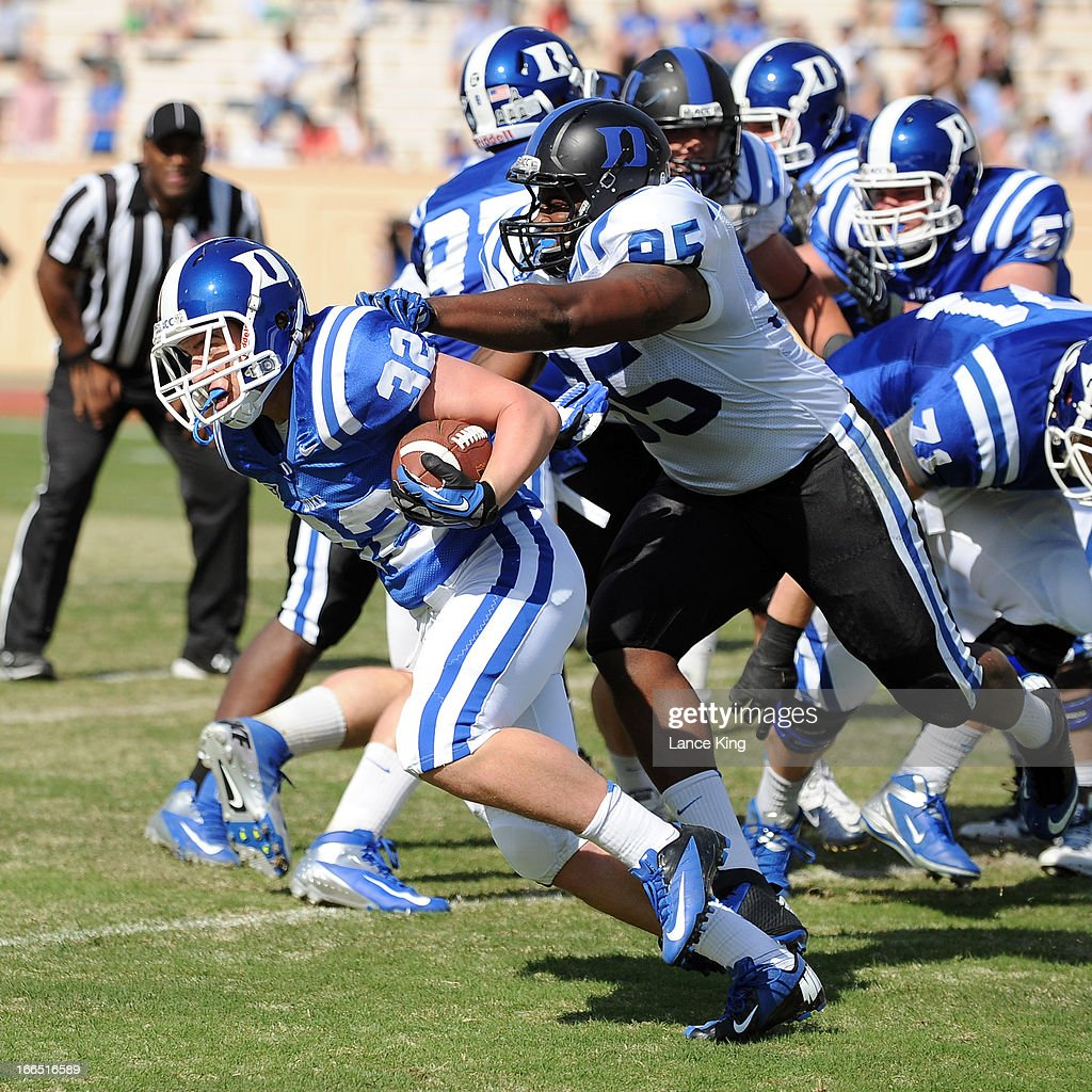 James Cockey #32 avoids a tackle by Jamal Wallace #95 of the Duke Blue Devils during their Spring Game at Wallace Wade Stadium on April 13, 2013 in Durham, North Carolina.