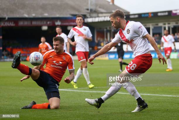 James Collins of Luton Town blocks a clearance from Mickey Demetriou of Newport County during the Sky Bet League Two match between Luton Town and...