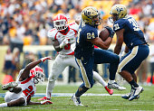 James Conner of the Pittsburgh Panthers evades a tackle while running with the ball in the first half against the Youngstown State Penguins during...