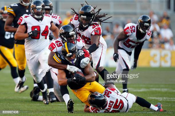 James Conner of the Pittsburgh Steelers rushes against Kemal Ishmael Deron Washington and Marcelis Branch of the Atlanta Falcons during a preseason...