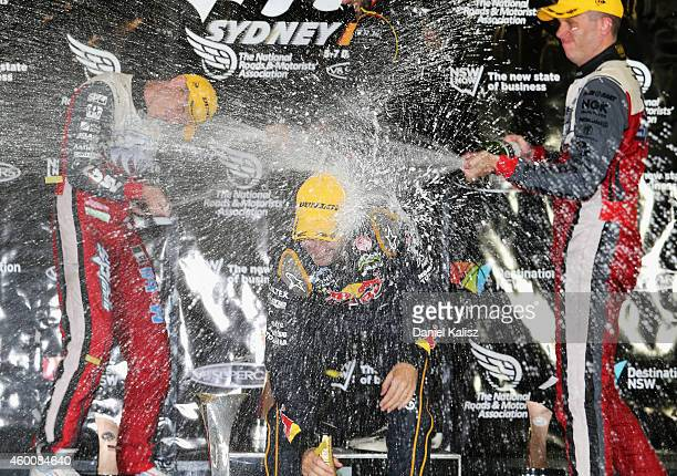James Courtney driver of the Holden Racing Team Holden celebrates on the podium with Jamie Whincup driver of the Red Bull Racing Australia Holden and...