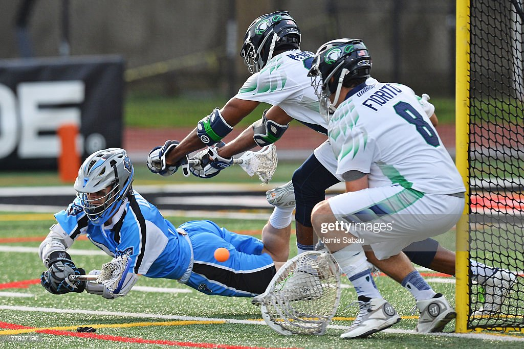 James Dailey of the Ohio Machine puts a shot on goal in the first quarter as Mark McNeill of the Chesapeake Bayhawks and Tyler Fiorito of the...