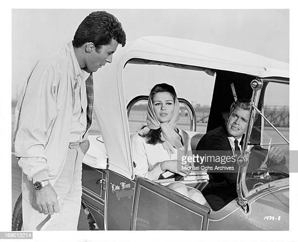 James Darren stands and talks to Pamela Tiffin and Doug McClure who is sitting in a car in a scene from the film 'The Lively Set' 1964