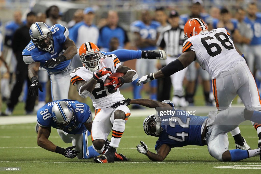 James Davis #28 of the Cleveland Browns runs for a short gain as Ko Simpson #30 and Amari Spievey #42 make the stop during the third quarter of the preseason game against the Detroit Lions at Ford Field on August 28, 2010 in Detroit, Michigan. The Lions defeated the Browns 35-27.
