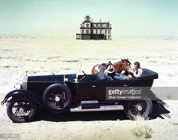 James Dean US actor on sitting in the backseat of a vintage motor car stroking a horse which stands beside the vehicle a large house stands isolated...