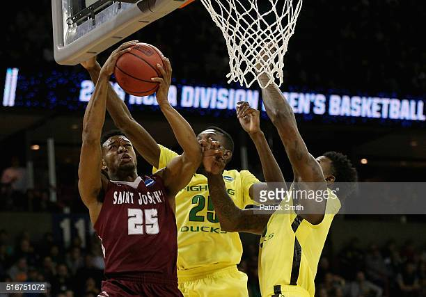 James Demery of the Saint Joseph's Hawks shoots against Chris Boucher and Jordan Bell of the Oregon Ducks in the first half during the second round...