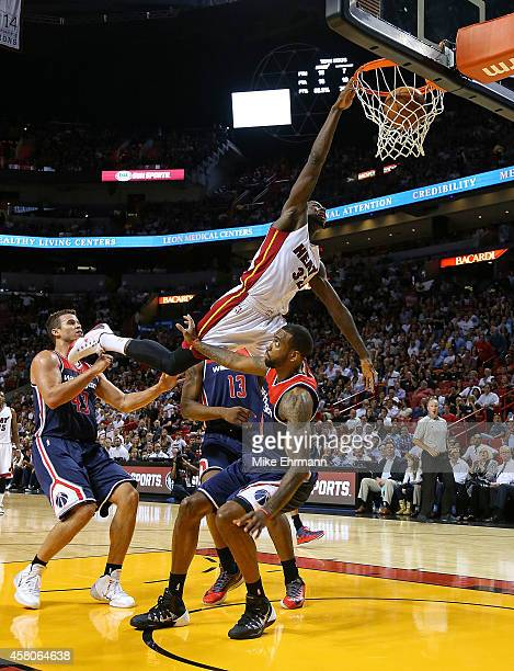 James Ennis of the Miami Heat dunks over Rasual Butler of the Washington Wizards during the Opening night game at American Airlines Arena on October...
