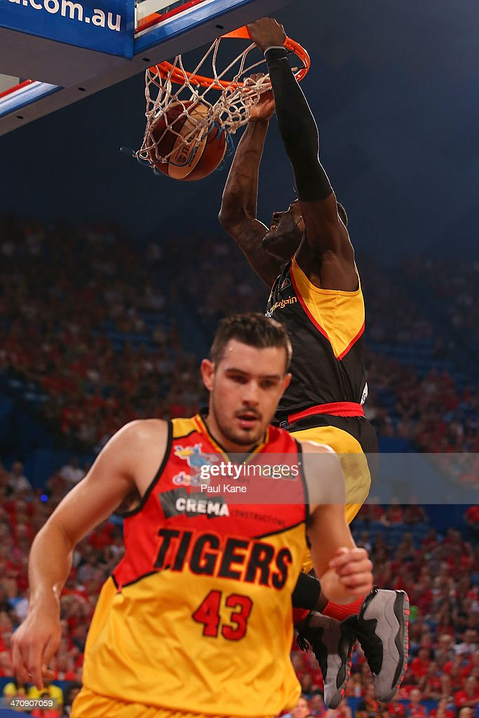 James Ennis of the Wildcats dunks the ball against Chris Goulding of the Tigers during the round 19 NBL match between the Perth Wildcats and the Melbourne Tigers at Perth Arena on February 21, 2014 in Perth, Australia.