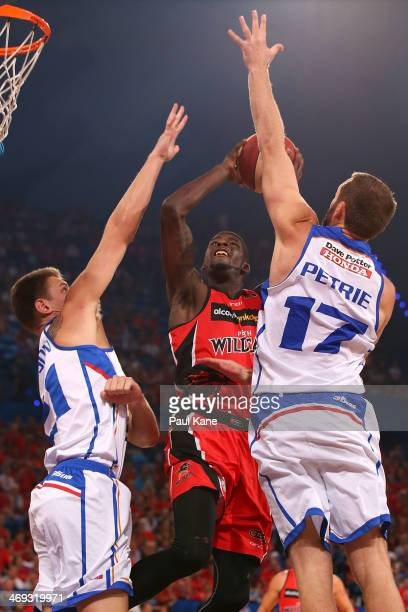 James Ennis of the Wildcats lays up against Daniel Johnson and Anthony Petrie of the 36ers during the round 18 NBL match between the Perth Wildcats...