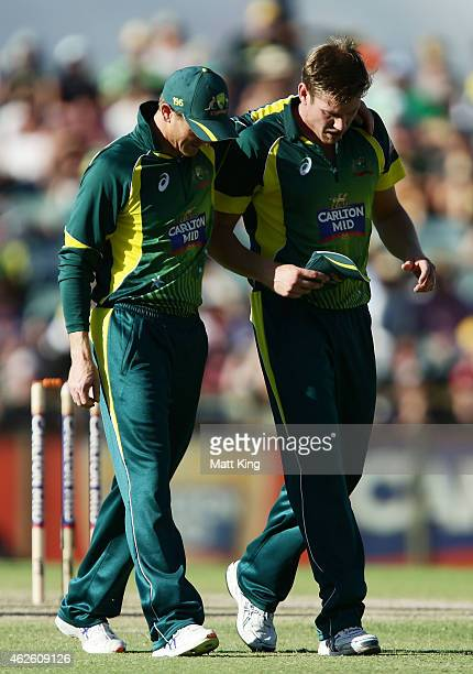 James Faulkner of Australia is consoled by Australian captain George Bailey as he leaves the field injured during the final match of the Carlton Mid...