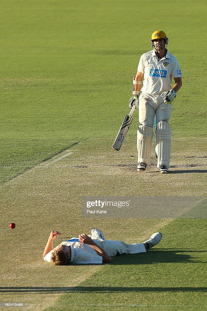 James Faulkner of the Tigers lies on the wicket after after being struck by the ball as Ryan Duffield of the Warriors looks on during day three of the Sheffield Shield match between the Western Australia Warriors and the Tasmania Tigers at WACA on February 23, 2013 in Perth, Australia.