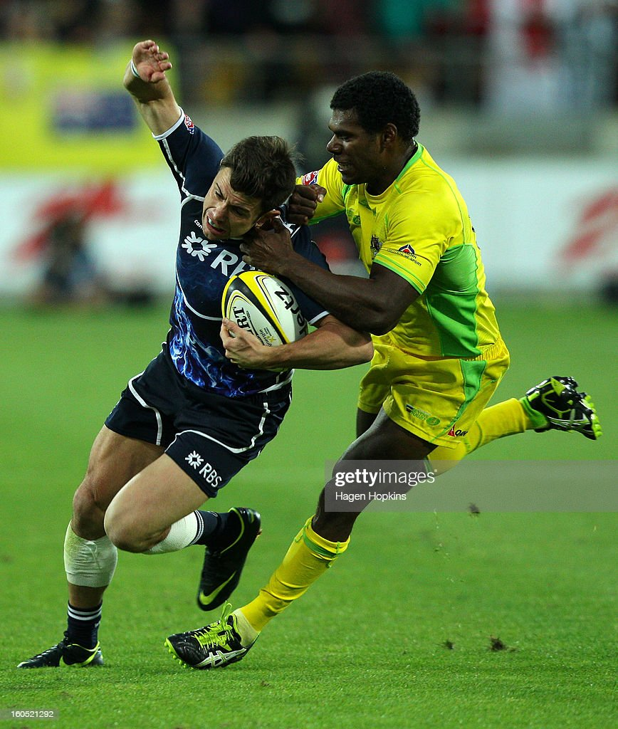 James Fleming of Scotland is tackled by Shannon Walker of Australia in the final plate match between Scotland and Australia during the 2013 Wellington Sevens at Westpac Stadium on February 2, 2013 in Wellington, New Zealand.