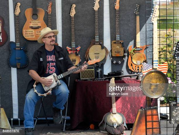 James Floyd from Pensacola FL demonstrates on one of his handcrafted fullyplayable musical instruments made from found and recycled objects calling...