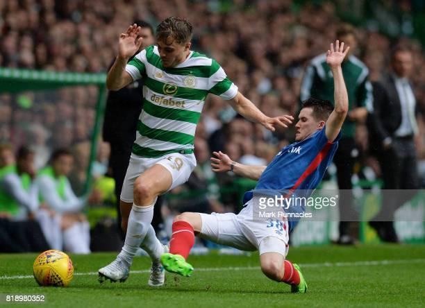 James Forrest of Celtic is challenged by Paul Smyth of Linfield during the UEFA Champions League Qualifying Second Round Second Leg match between...